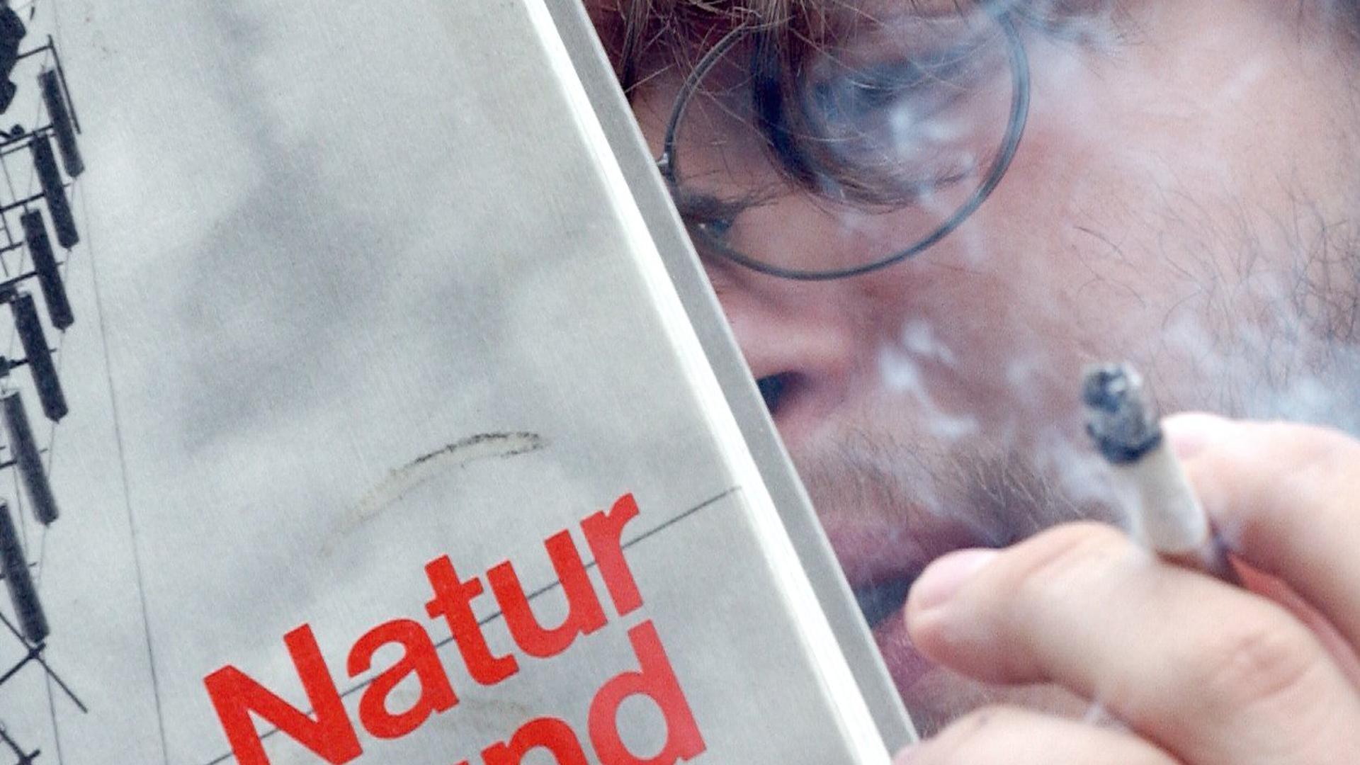 """Gymnasiast Mutwin raucht, während er in einem Schulbuch liest (Foto vom 09.07.2003). An vielen Gymnasien herrscht Rauchverbot. Raucher müssen den Pausenhof verlassen, um zu rauchen, während andere Gymnasien Raucherzimmer oder Raucherbereiche auf den Schulhöfen einrichten. Foto:Achim Scheidemann dpa/lnw (zu lnw-KORR: """"Raucher hier, Nichtraucher dort"""" - Zweifel an rauchfreien Schulen"""" vom 15.07.2003)"""
