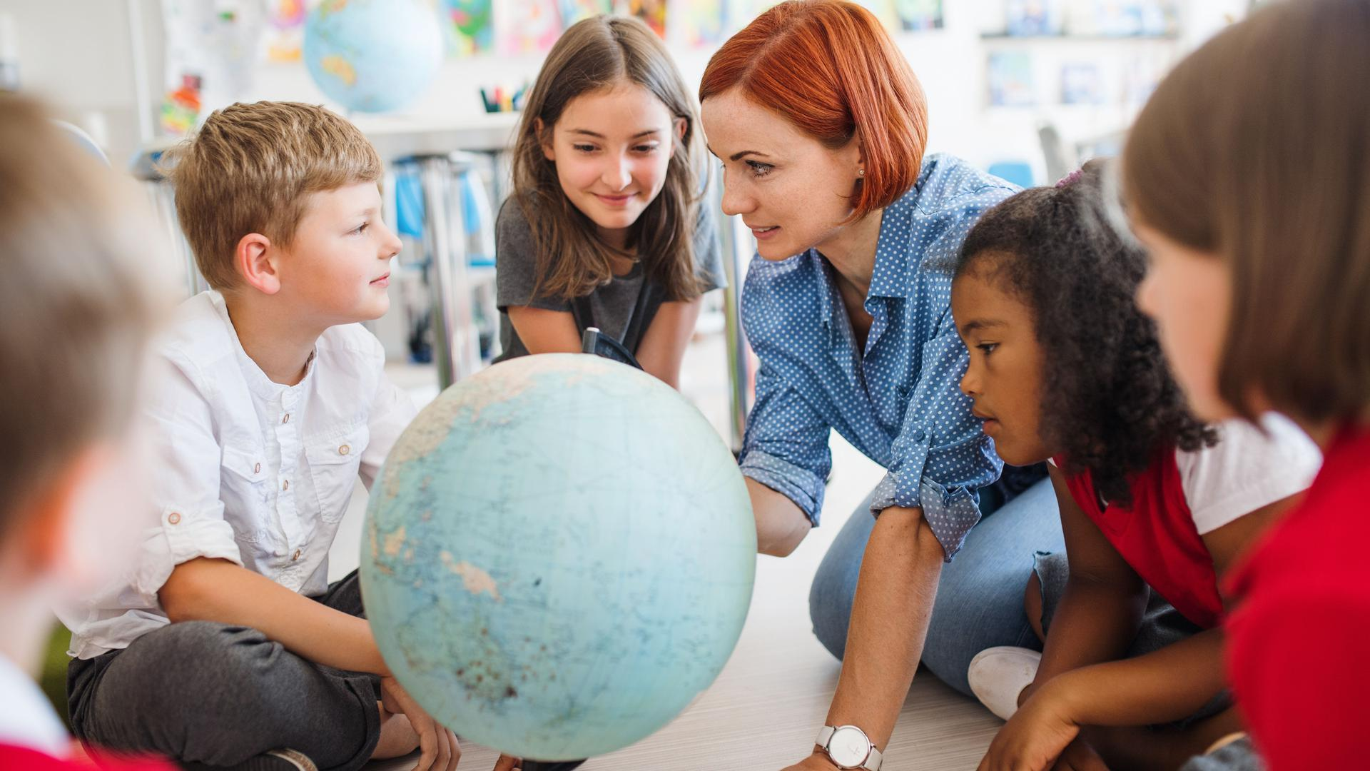 A group of small school kids with unrecognizable teacher sitting on the floor in class, learning geography.