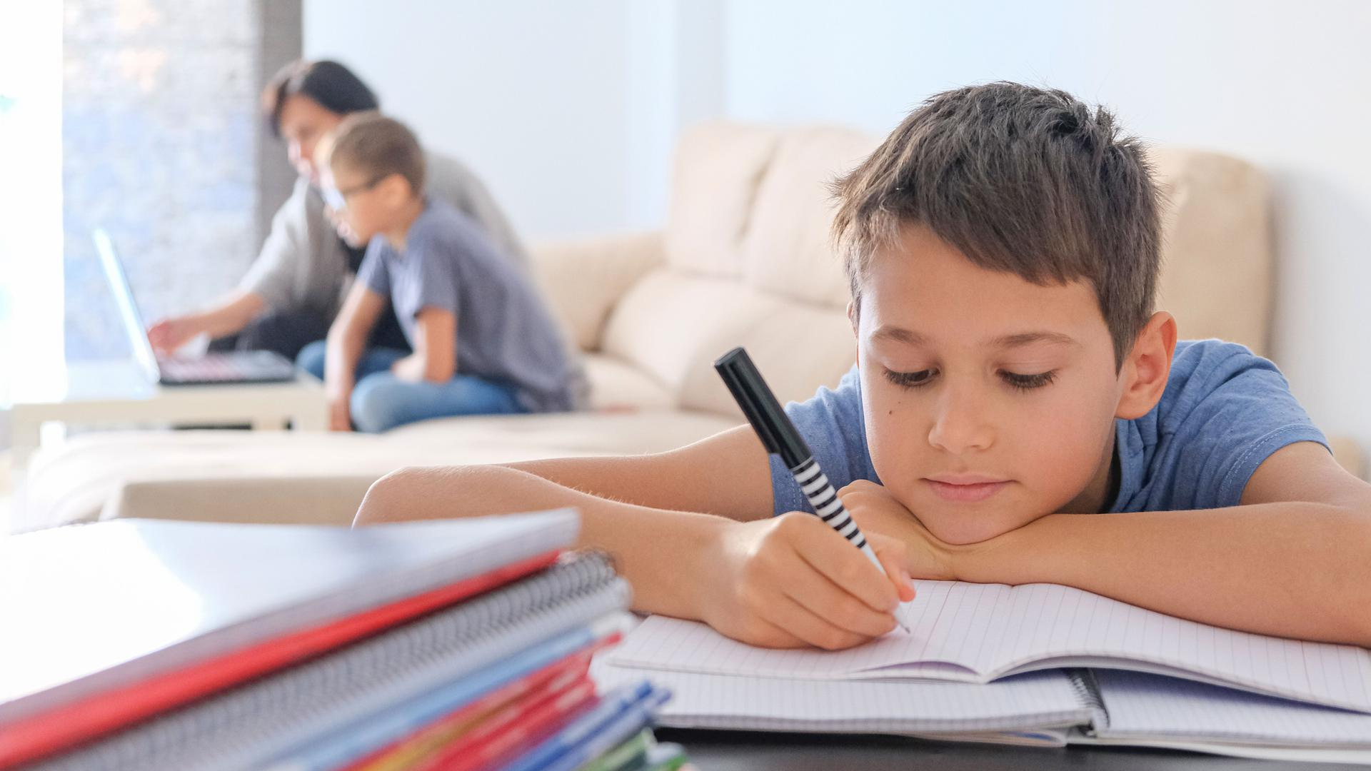 Learning at home, online learning, self quarantine concept. Family at home. Children doing homework with books, textbooks and with computer online, mother help to kids.