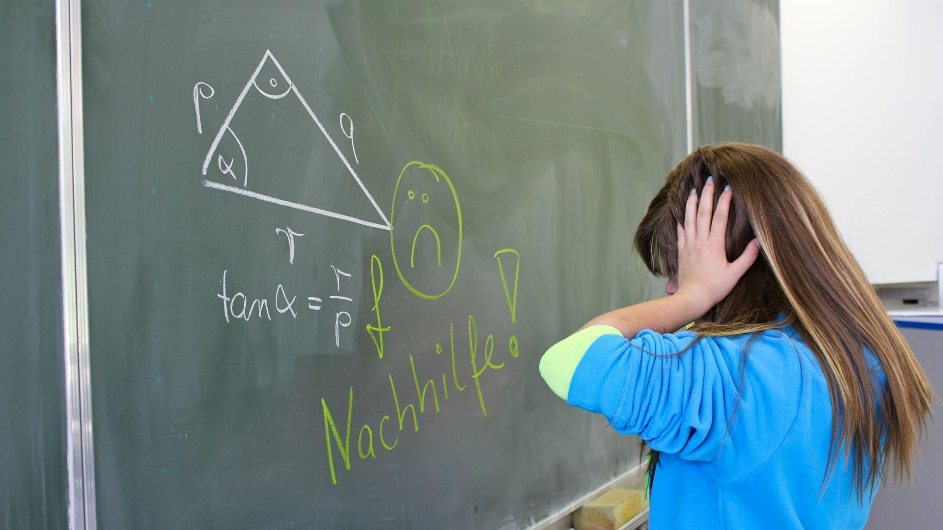 Kind verzweifelt an der Schultafal an einer Mathematik-Aufgabe
