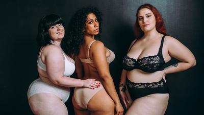 Drei mehrgewichtige Frauen schauen für ein Fotoprojekt selbstbewusst in die Kamera.