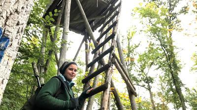 Junge Frau mit Gewehr steht im Wald vor einem Hochsitz aus Holz