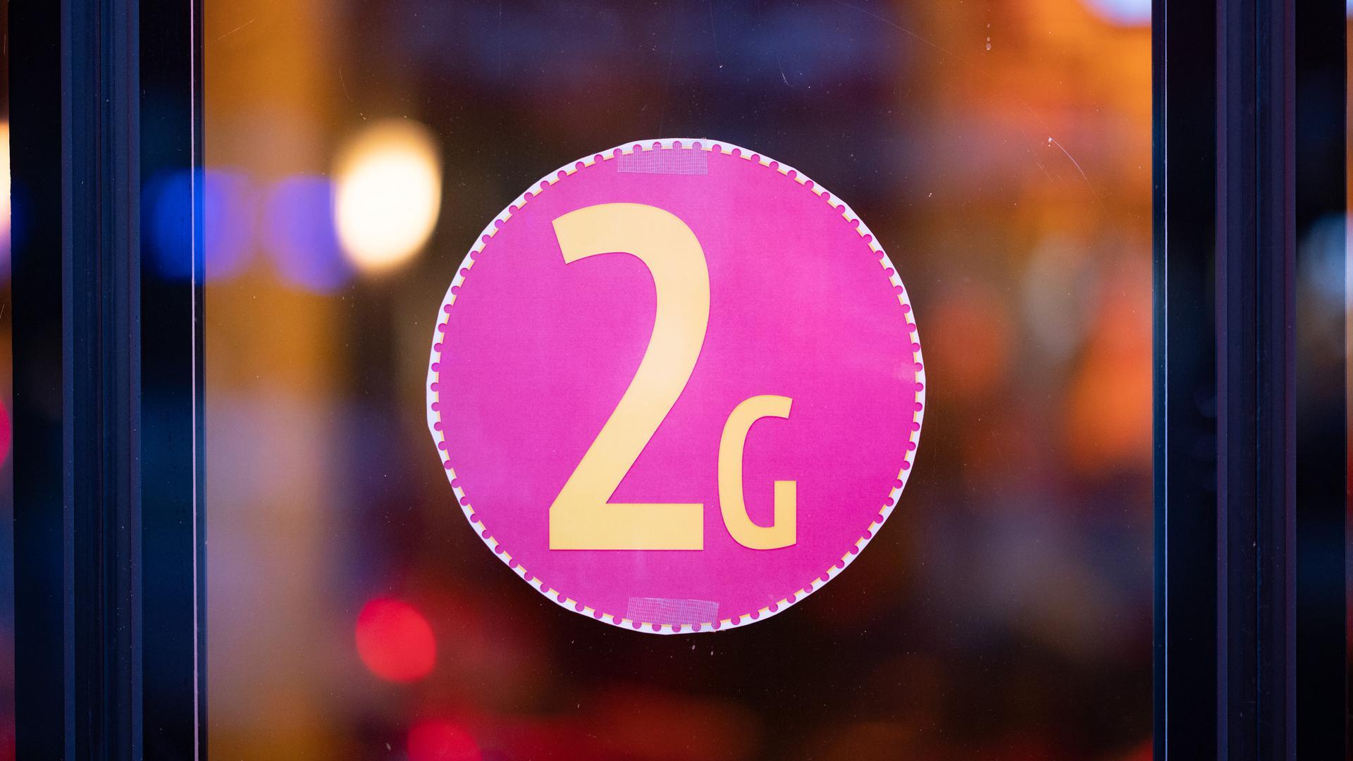 """Ein Aufkleber mit der Aufschrift """"2G"""" ist am Eingang von Schmidts Tivoli Theater zu sehen."""