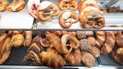 Ein Hand nimmt in einer Bäckerei eine Brezel aus einer Auslage.