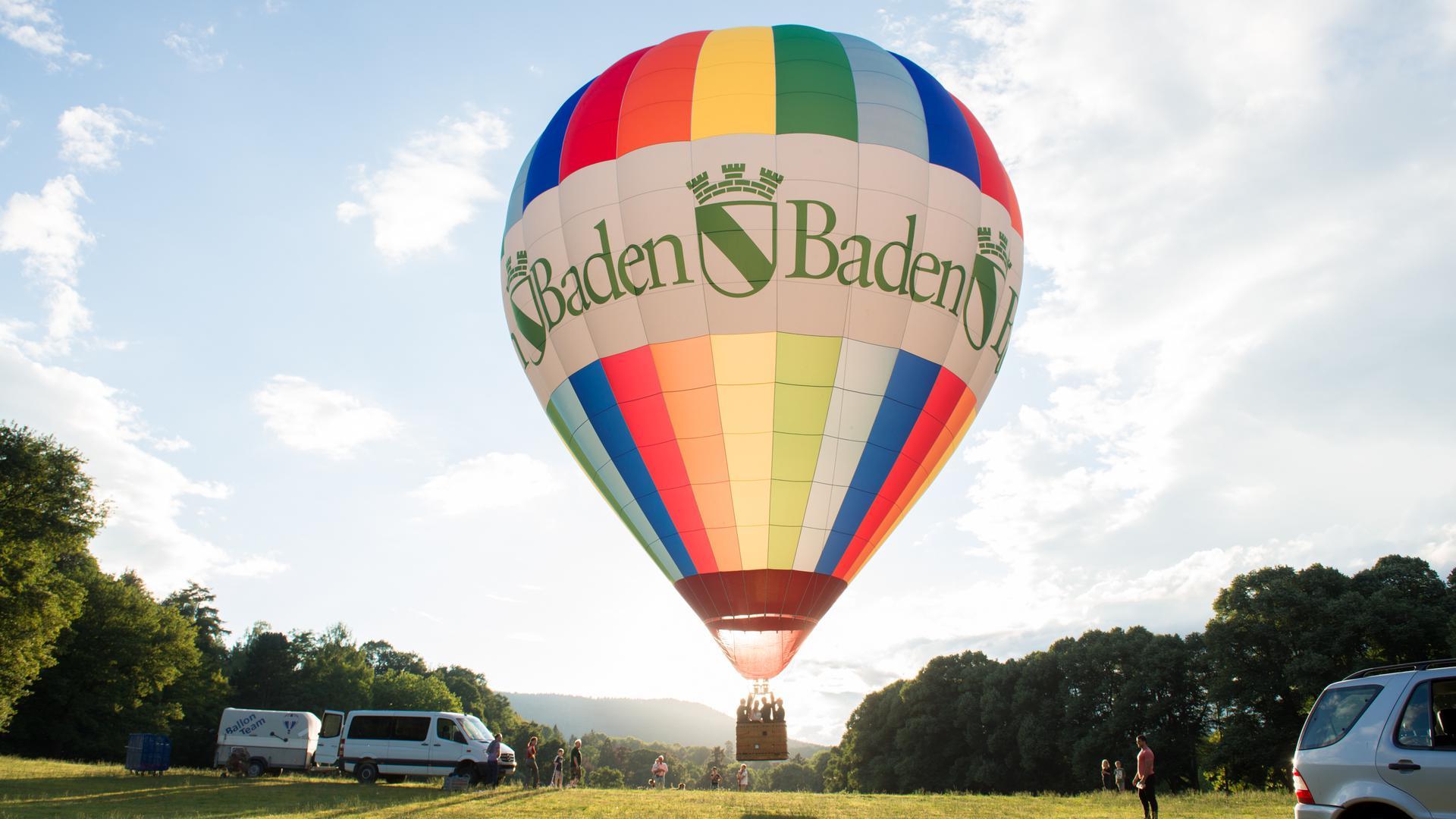 """Heißluftballon mit Aufschrift """"Baden-Baden"""" hebt auf einer von Bäumen gesäumten Wiese ab."""
