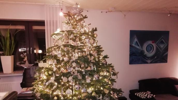 Weihnachtsbaum mit weißem Schmuck und brennenden Lichtern.