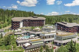 Das Hotel Vierjahreszeiten lieht vor einem üppigen Nadelwald.