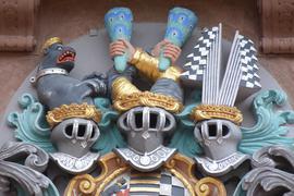 buntes Wandrelief mit drei Ritterhelmen