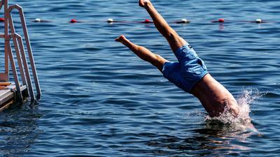 Ein junger Mann springt von einer Schwimmplattform in einen See.