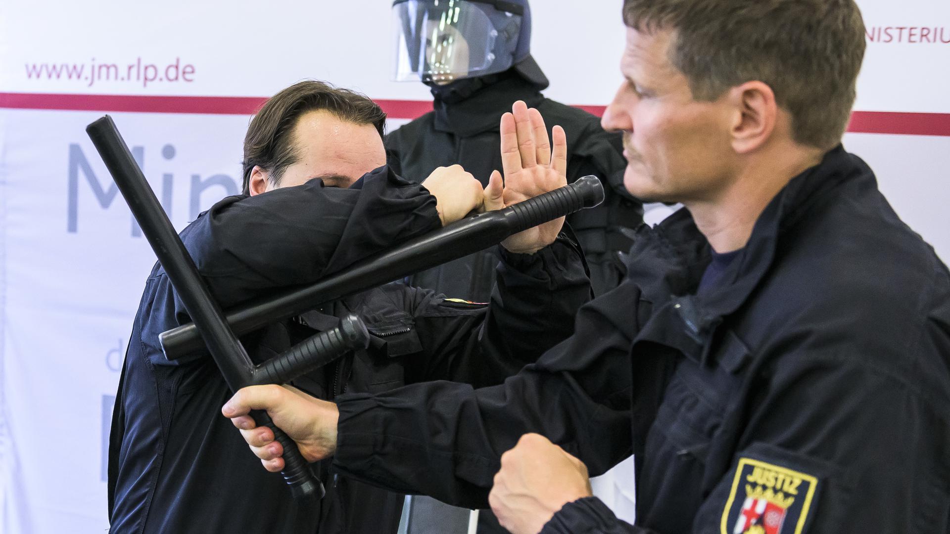 Bei einer Pressekonferenz im Ministerium der Justiz führen zwei Justizvollzugsbeamten John Klein den Einsatz des neuen Einsatzstocks vor.