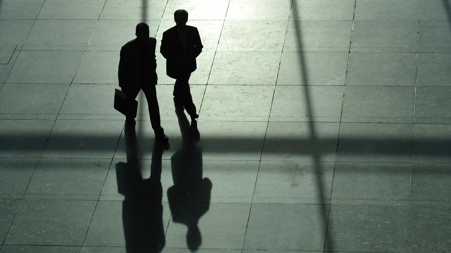 ARCHIV - 24.03.2010, Baden-Württemberg, Stuttgart: Zwei Männer im Anzug, von denen einer einen Aktenkoffer trägt, werfen lange Schatten. (zu dpa «Regierung gibt mehr als 178 Millionen Euro für externe Berater aus») Foto: Uwe Anspach/dpa +++ dpa-Bildfunk +++   Verwendung weltweit
