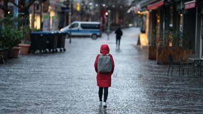 Eine Frau geht morgens durch eine nahzu menschenleere Innenstadt.
