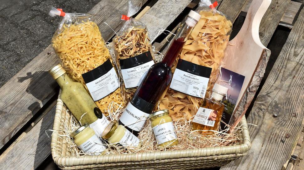 Geschenkkorb mit Nudelpackungen, Whisky, Senf und einem Holzbrett