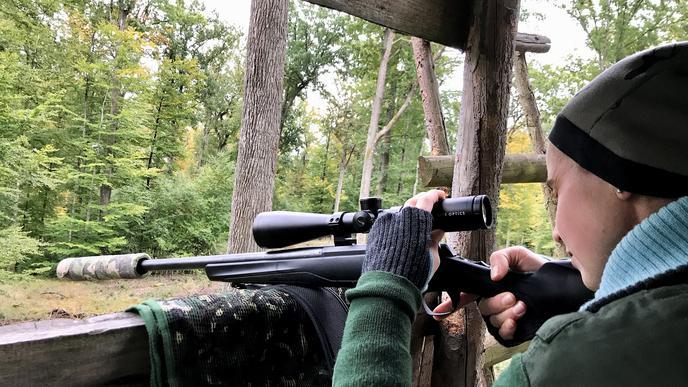 Frau mit Gewehr auf einem Hochsitz.