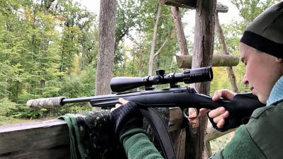 Junge Frau sitzt mit dem Gewehr im Anschlag auf dem Hochsitz.