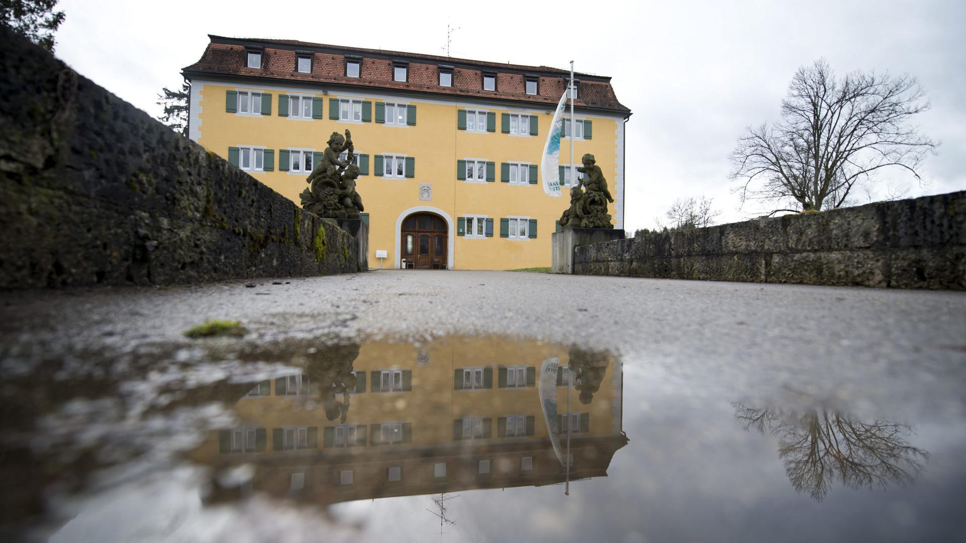 Das Schloss Grafeneck spiegelt sich in einer Pfütze.