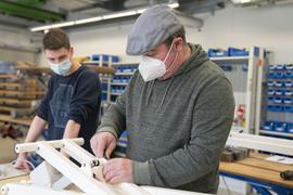 Beschäftigte der HWK bauen eine medizinische Liege.