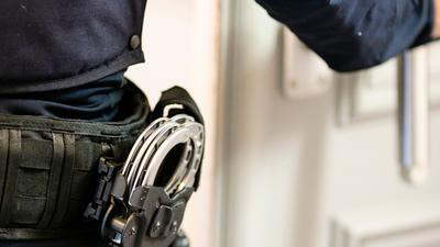 Handschellen sind an einem Gürtel eines Beamten befestigt.