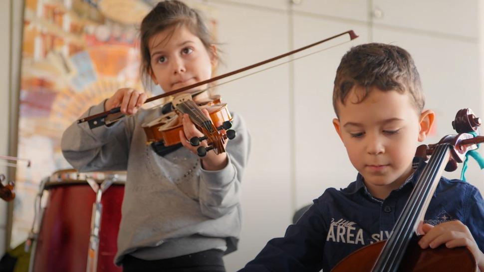 Zwei Kinder mit Streichinstrumenten.