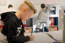 Kind schreibt an einem Schreibtisch in ein Arbeitsheft. Im Hintergrund andere Schüler an Schreibtischen mit Aktenordner-Regalen.