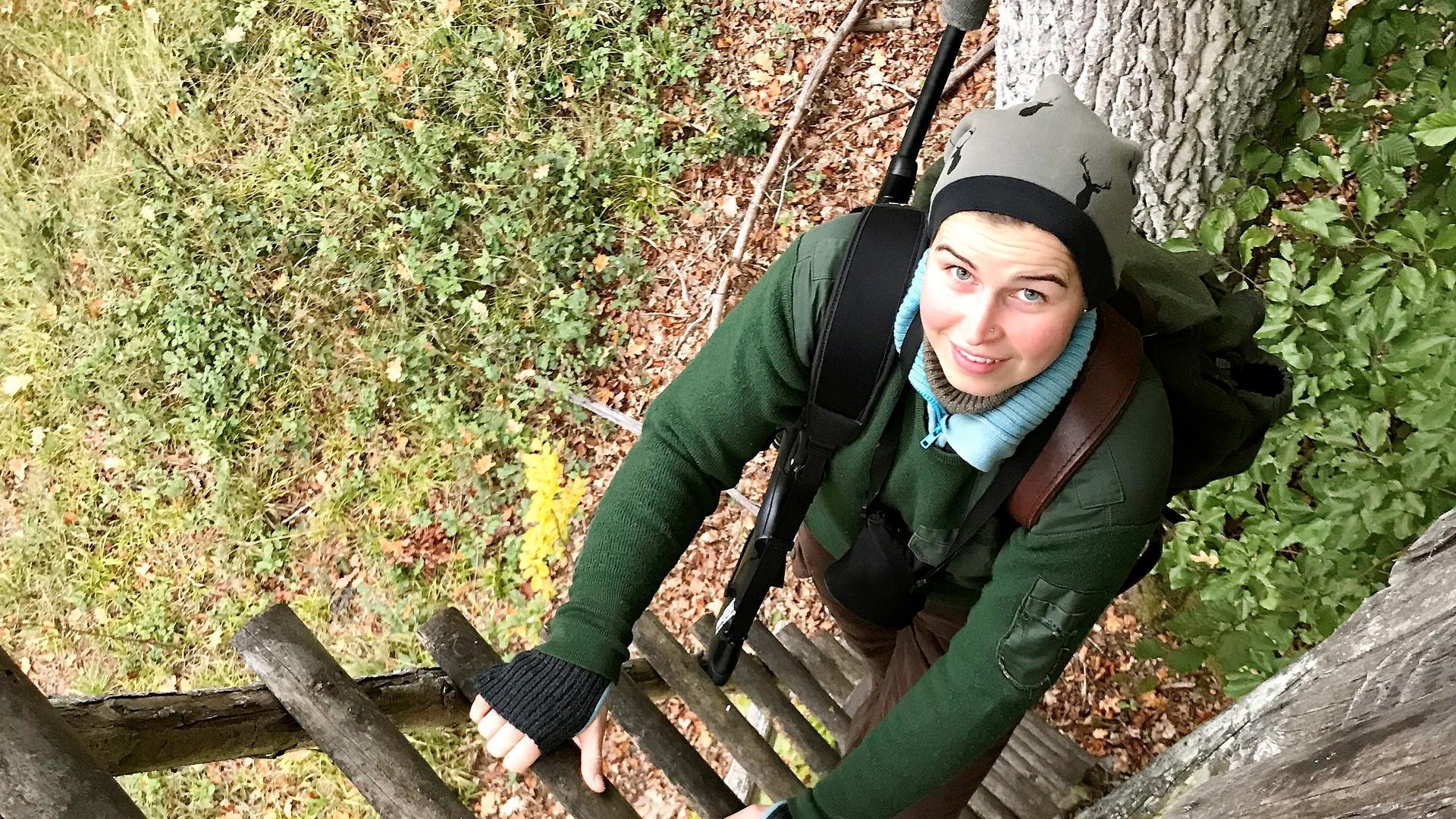 Blick von oben auf Frau, die eine Leiter hochsteigt.