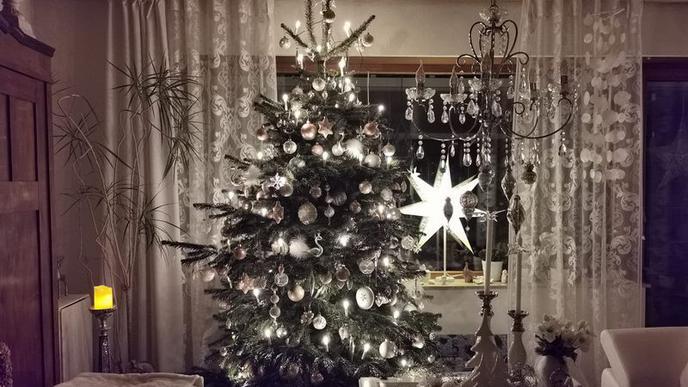 Ein in Weiß geschmückter Baum steht neben einem Kronleuchter. Am Fenster im Hintergrund leuchtet ein Stern.