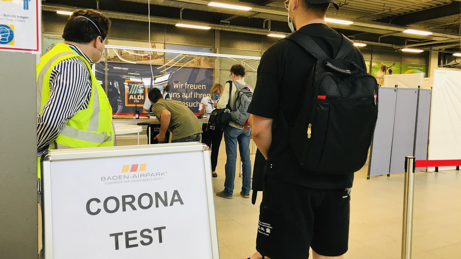 Menschen stehen vor einem kleinen und mit Stellwänden abgetrennten Bereich, in dem am Flughaen Karlsruhe/Baden-Baden kostenlose Corona-Tests erfolgen.