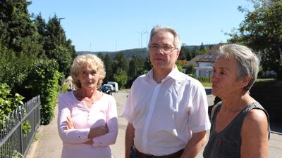 Drei Personen stehen an der Straße, dahinter sieht man Windräder.