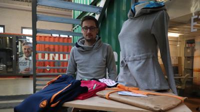 Fabian Krüger steht hinter einem Kleiderständer, auf dem Pullis und Jogginghosen liegen.