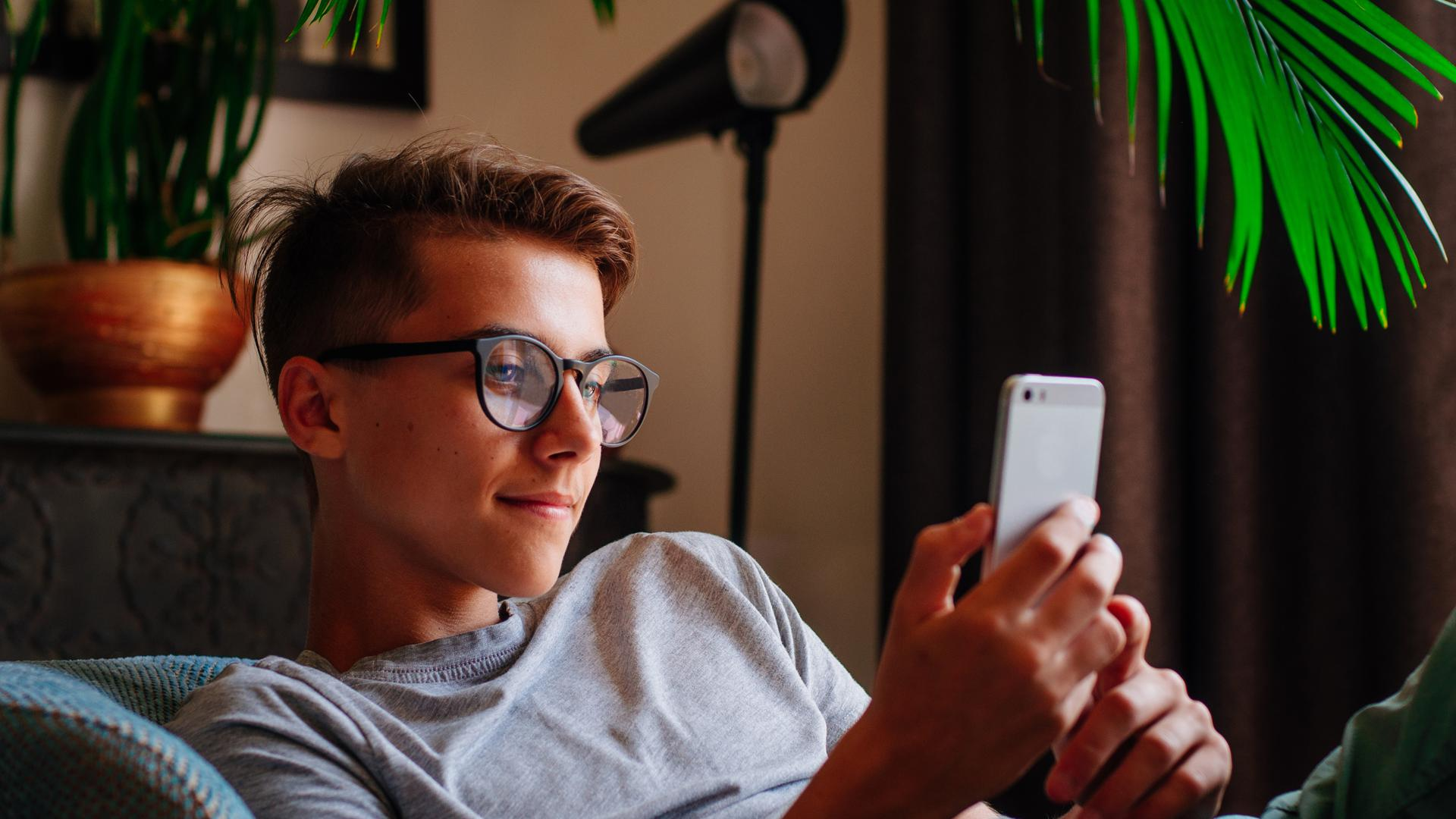 Generation Z concept. Smiling boy in glasses using smartphone sitting in the chair indoor.