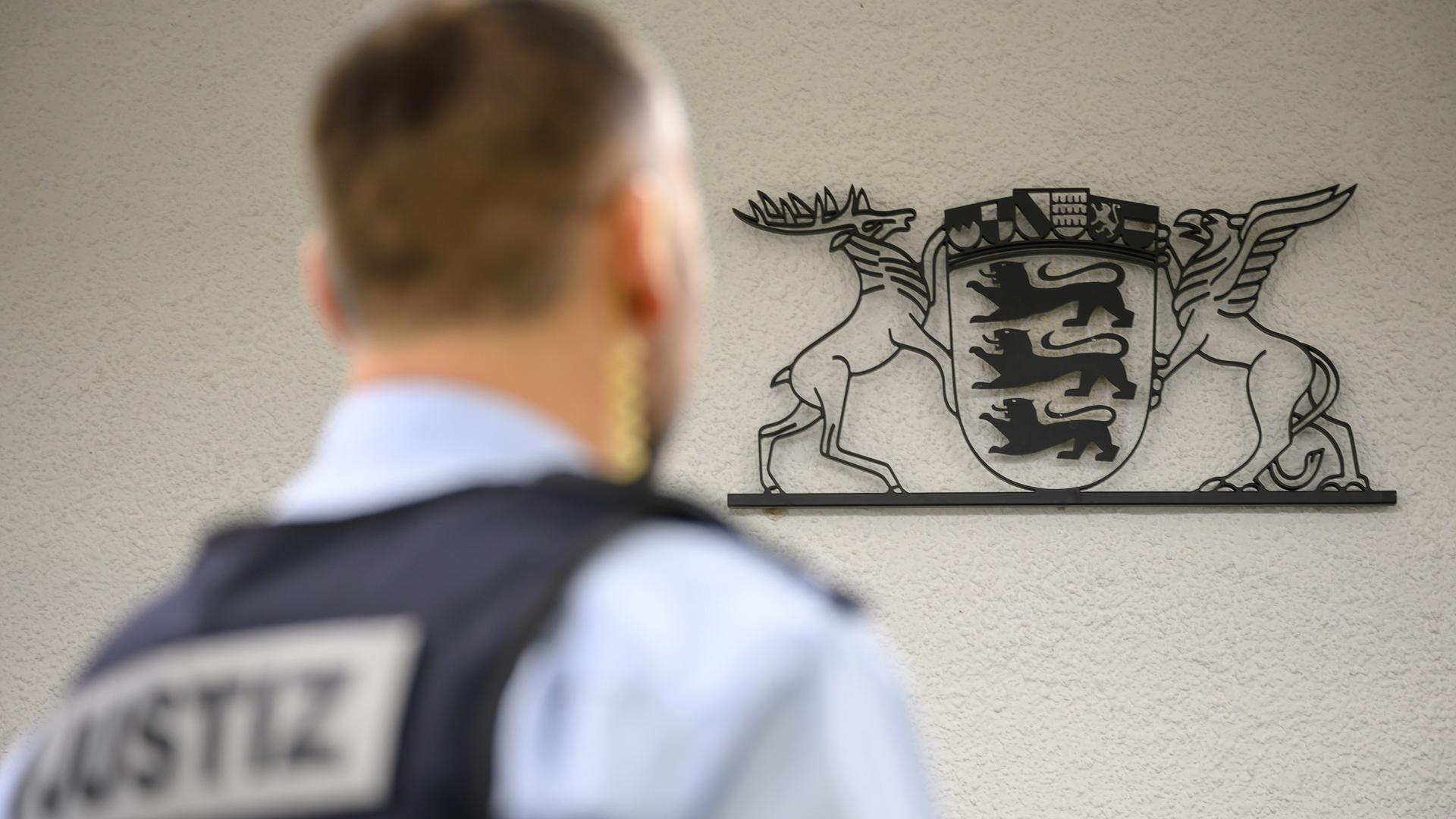 ARCHIV - Ein Justizbeamter steht in einem Gerichtssaal des Landgerichts (gestellte Szene). In dem Gebäude wird nach mehr als einem Dutzend Drohschreiben und einem versuchten Brandanschlag ein Urteil gegen ein Paar aus Stuttgart gesprochen werden. (zu dpa «Urteil nach Drohschreiben gegen Politiker erwartet») +++ dpa-Bildfunk +++