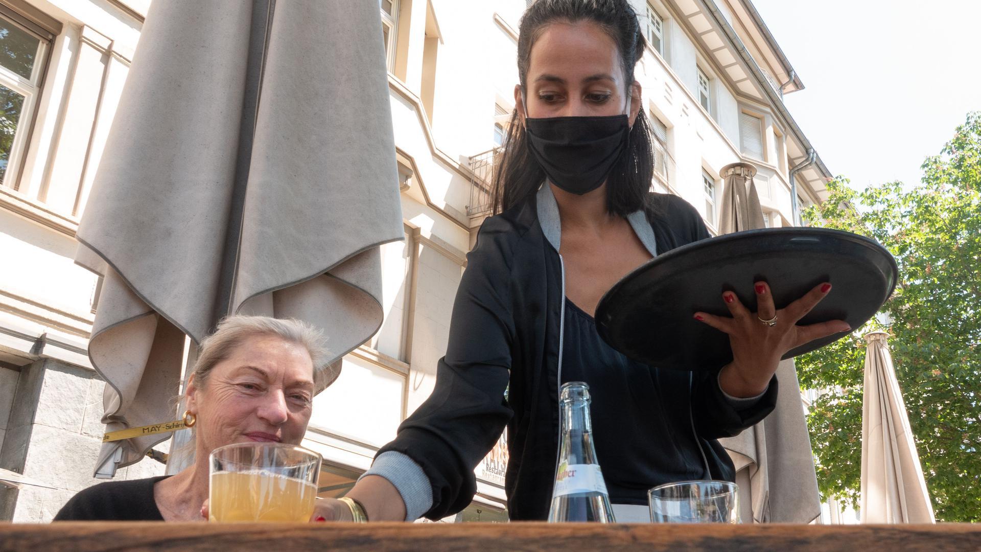 18.05.2020, Baden-Württemberg, Stuttgart: Eine Kellnerin mit Mundschutz stellt auf der Terrasse vor dem Café Kaiserbau einer Kundin ein Getränk auf den Tisch. Speise-Gaststätten, Ferienwohnungen und Campingplätze dürfen ab dem 18.05.2020 unter Einhaltung bestimmter Auflagen wieder für Ihre Gäste öffnen. Foto: Gregor Bauernfeind/dpa +++ dpa-Bildfunk +++ | Verwendung weltweit