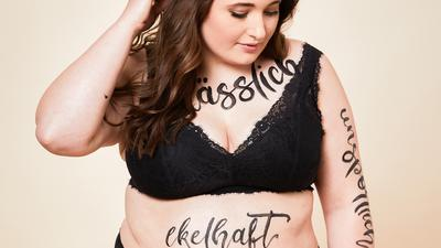 """Julia Kremer trägt einen schwarzen BH und eine schwarze Unterhose. Auf ihrem Dekolleté ist mit schwarzer Farbe das Wort """"hässlich"""" geschrieben. Auf ihrem Bauch steht das Wort """"ekelhaft""""."""