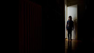 Ein junges Mädchen steht am Ende eines dunklen Flures.