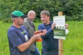 Schutz der Artenvielfalt: Landwirt Rainer Hummel (links) und WWF-Programmleiter Lukas Wortmann installieren eine Informationstafel auf dem Degenfelder Galgenberg, im Hintergrund Edeka-Südwest-Geschäftsführer Jürgen Mäder.