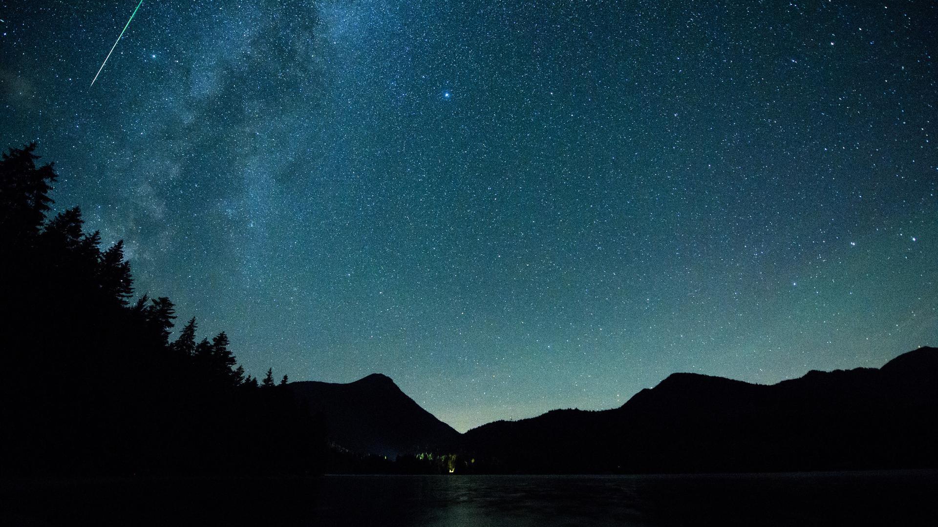 Eine Sternschnuppe leuchtet neben der Milchstraße am Himmel über dem Walchensee. Jedes Jahr im August sind im Sternschnuppenstrom der Perseiden zahlreiche Sternschnuppen zu sehen.
