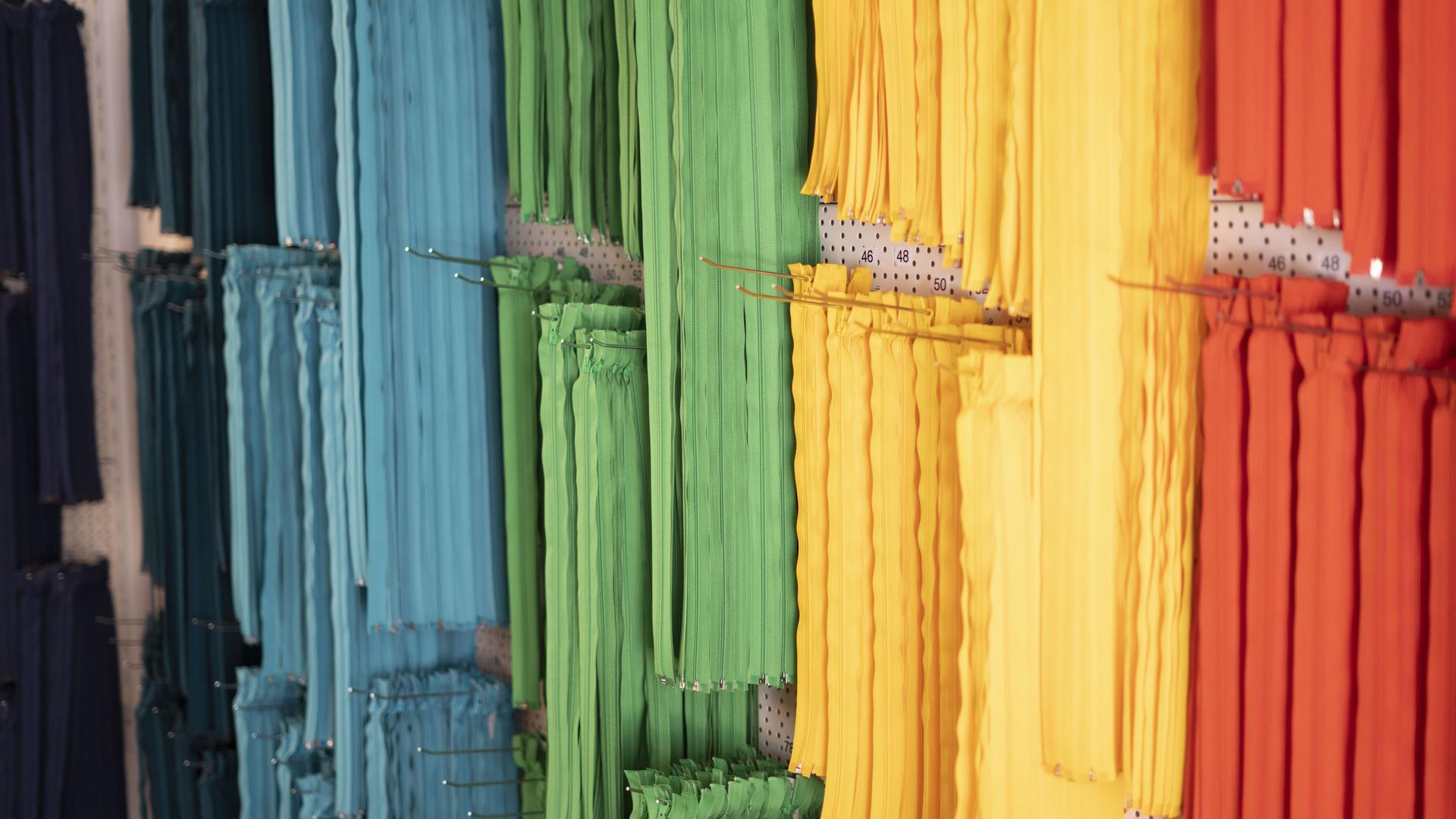 Reißverschlüsse in allen Regenbogenfarben hängen an der Wand der Schneiderei.