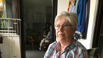 Roswitha Goller sitzt auf einem Stuhl und hat Fotos ihres Bruders in der Hand.