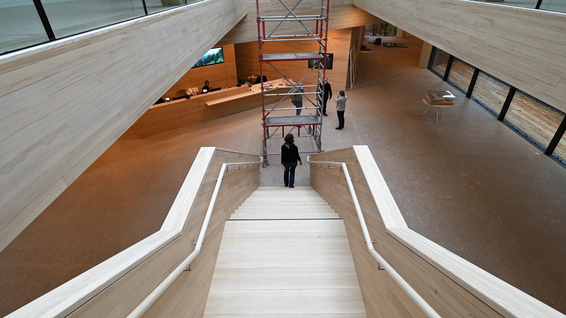 Die Holztreppe mit Oberlicht steht im Zentrum des Foyers.