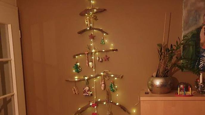 Ein Mobile aus Treibholz ist in Tannenbaumform angeordnet und mit Lichtern und Christbaumkugeln geschmückt.