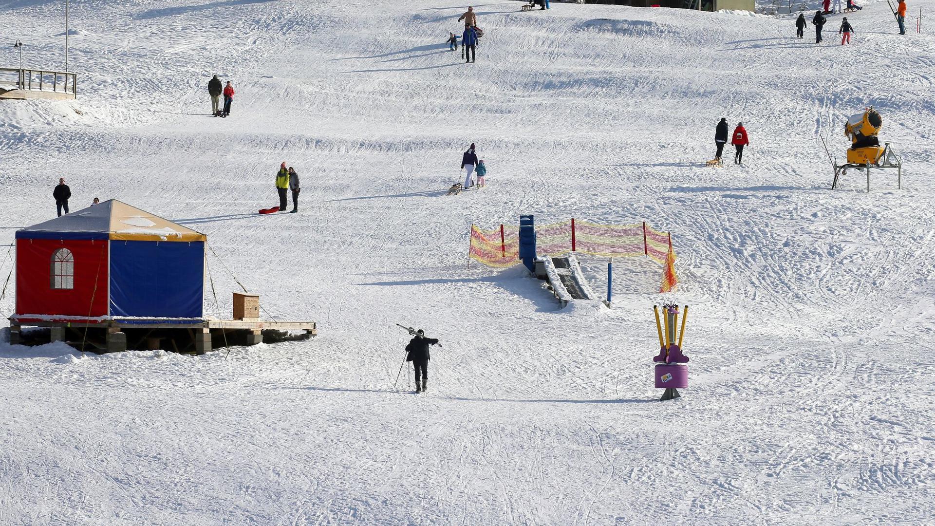Ausflügler mit Schlitten und Ski vergnügen sich auf einer Piste im Sonnenschein.