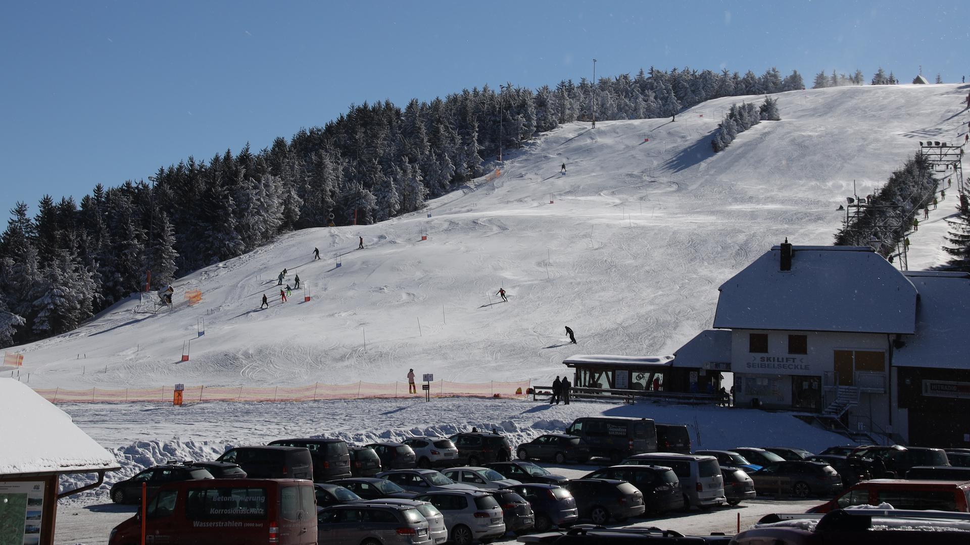 Autos stehen auf einem Parkplatz vor dem Skihang Seibelseckle
