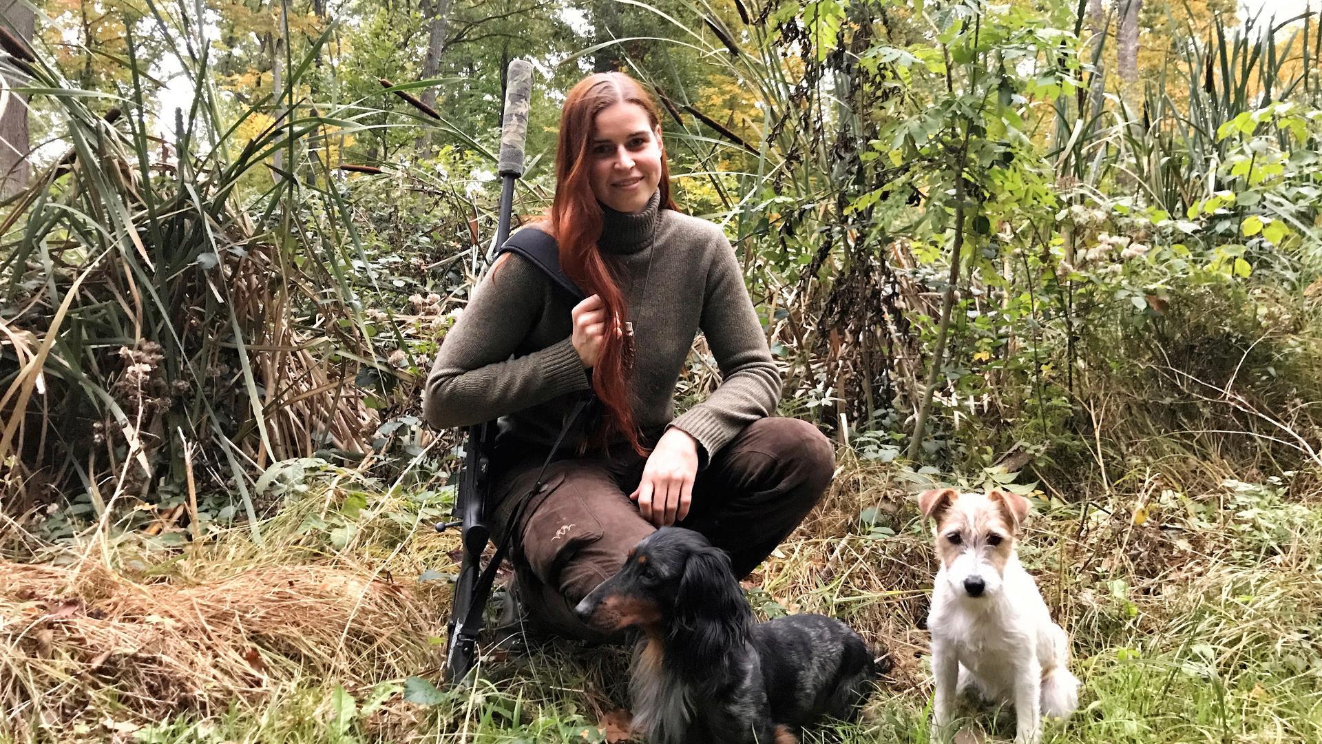 Junge Frau hat ein Gewehr umgehängt und kniet auf einer Wiese mit Schilfpflanzen im Hintergrund. Vor ihr sitzen zwei Hunde.