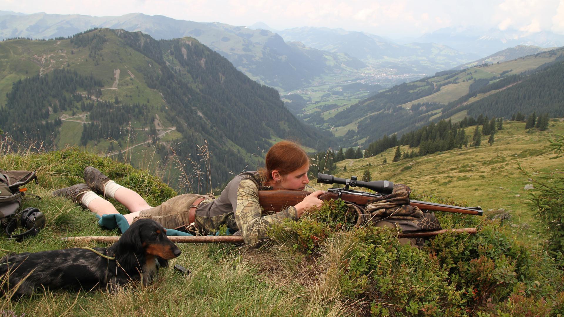 Frau liegt mit Gewehr im Anschlag auf einem Stein, daneben ein Hund. Im Hintergrund Alpenpanorama.