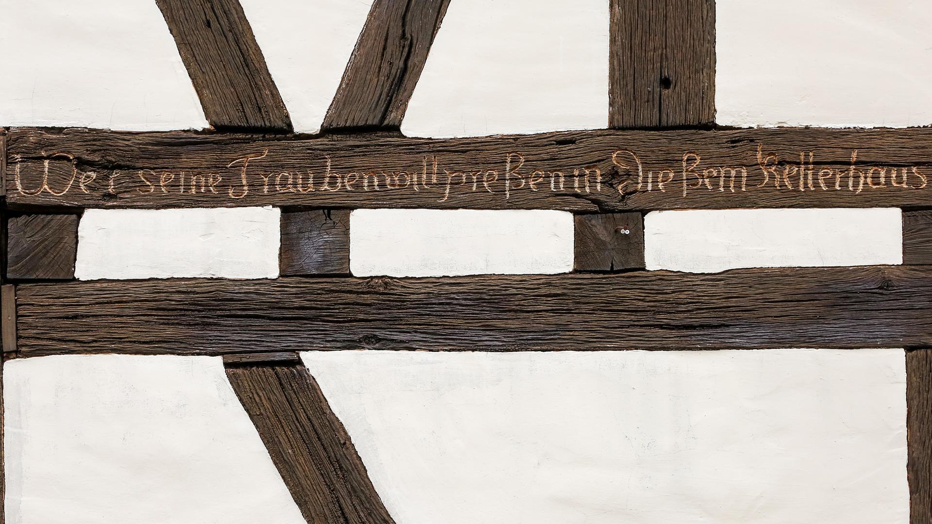 """Eine Wand mit Fachwerk, in der Holz ist folgender Spruch geschnitzt: """"Wer seine Trauben will preßen in diesem Kelterhaus"""""""