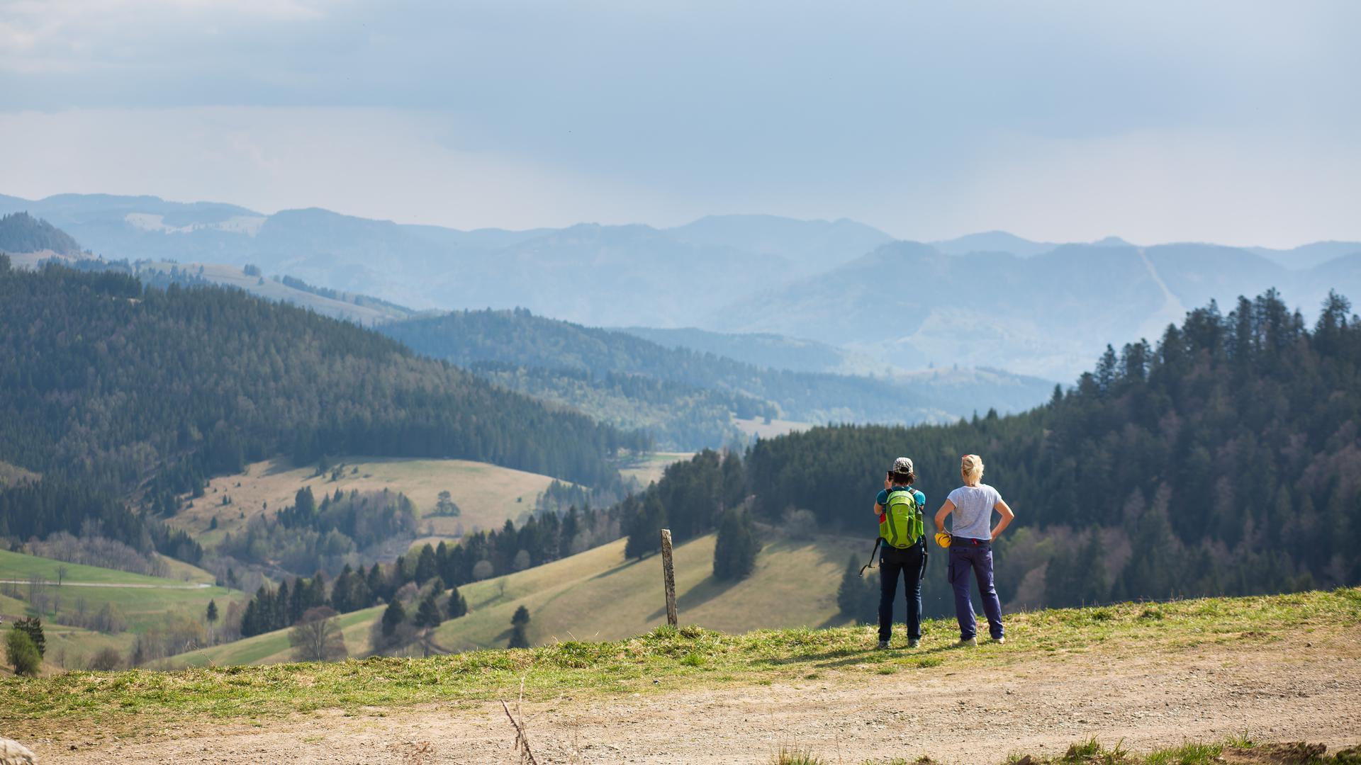 Zwei Frauen stehen nahe dem Nonnenmattweiher auf einem Parkplatz und blicken in die Landschaft.