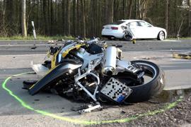 Ein völlig demoliertes Motorrad liegt am Straßenrand.
