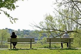 """Ein Mann und eine Frau sitzen mit dem größtmöglichen Abstand auf zwei Bänken am Ufer der Ruhr. (zu dpa """"Neue Coronaschutz-Verordnung in NRW: Jetzt auch mit Mindestabstand"""") +++ dpa-Bildfunk +++"""