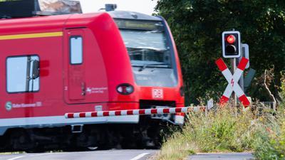 Eine S-Bahn der Deutschen Bahn (DB) fährt an einem Bahnübergang mit einer roten Ampel vorbei.