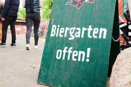 """""""Biergarten offen!"""" steht auf einem Schild beim Einlass eines Biergartens"""